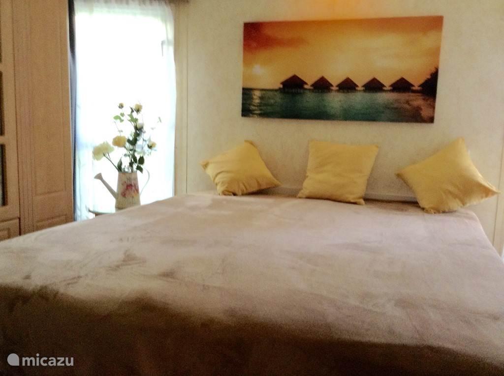 De grote slaapkamer met ruim tweepersoons bed en extra toilet.