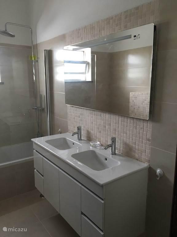 groot badkamer met bad, biddet, en double wastafel