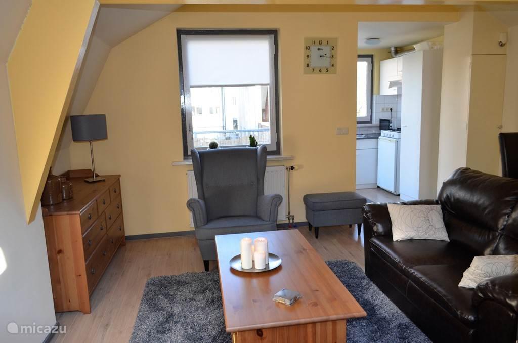 Een gezellige huiskamer met op de achtergrond de keuken, waar het dakterras aan grenst.