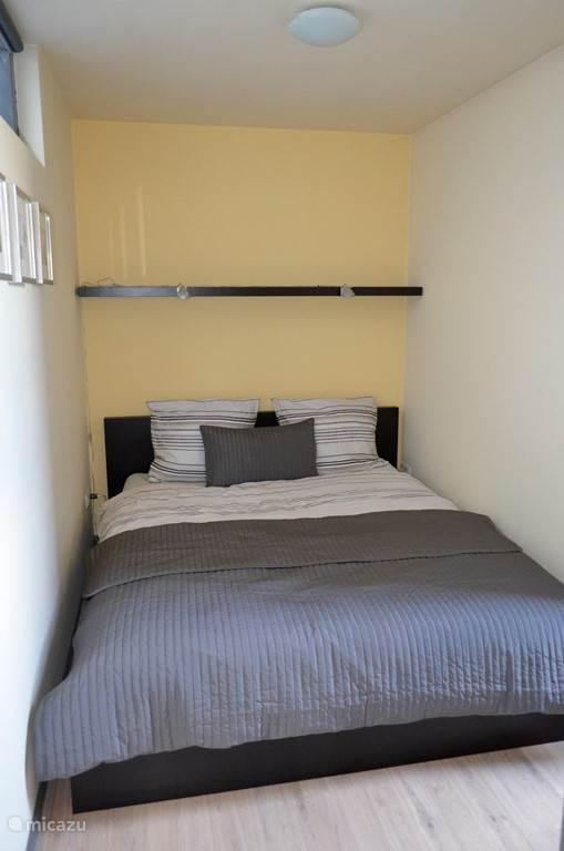 Een aparte slaapkamer met een tweepersoons bed.