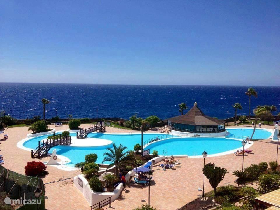 zwembaden met ligbedden en gratis parasols met uitzicht  op zee.