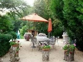 Terras met eettafels, parasols, BBQ en ligbedden