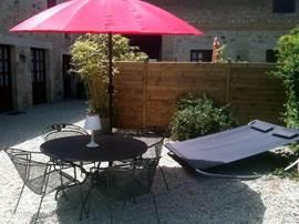 Terras van gite 2. Alle gites en het Pavillon hebben een eigen afgeschermd privéterras met comfortabel tuinmeubilair, parasol, ligbedden en BBQ