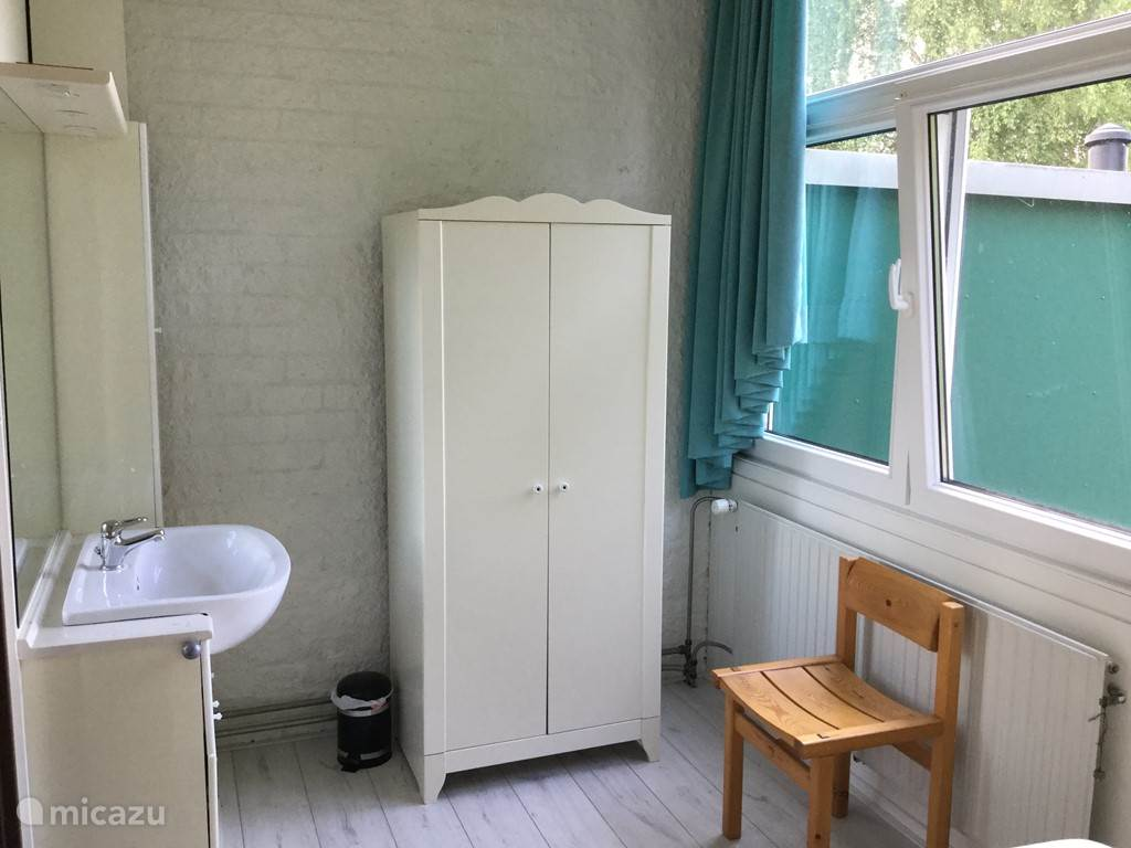 Slaapkamer op de 1e etage met vaste wastafel en kledingkast.