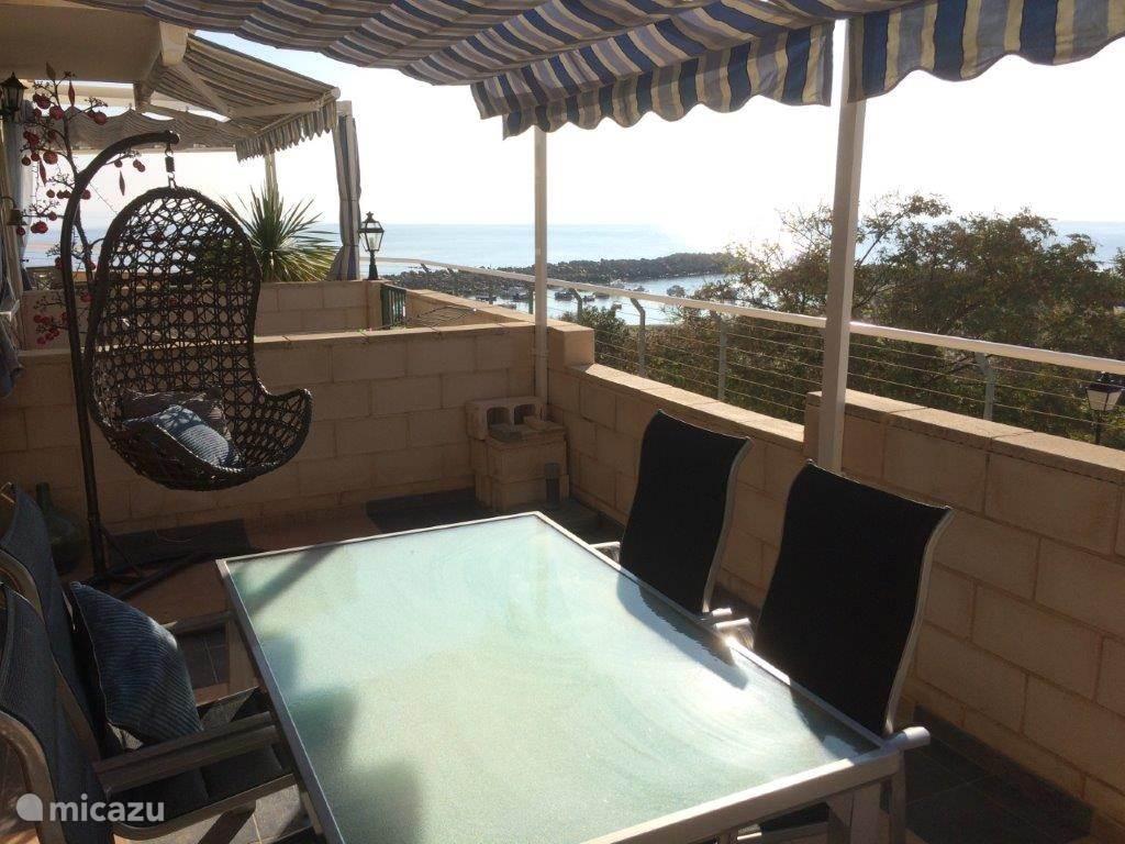 Terras met zeezicht en zicht op zwembad, speeltuin.