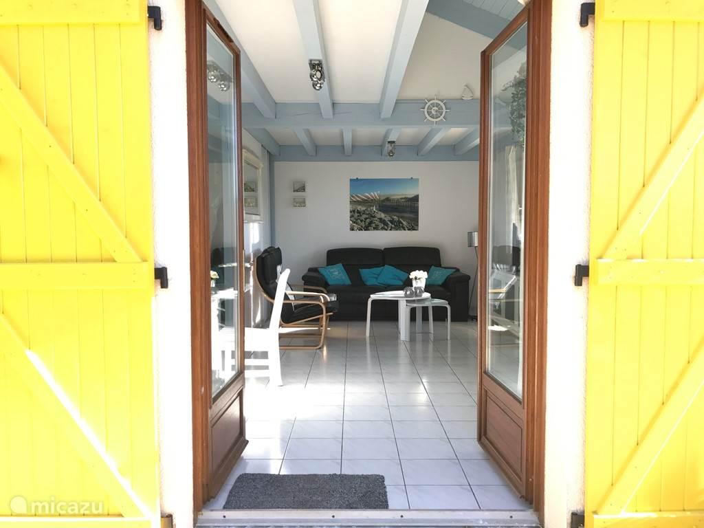 Entree van woning met een kijkje in de woonkamer