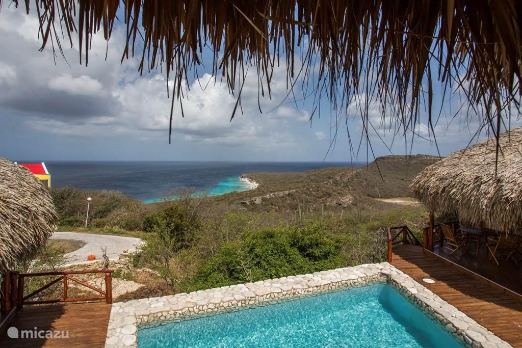 Uitzicht over het zwembad en de zee vanaf de porch van de grote palapa.