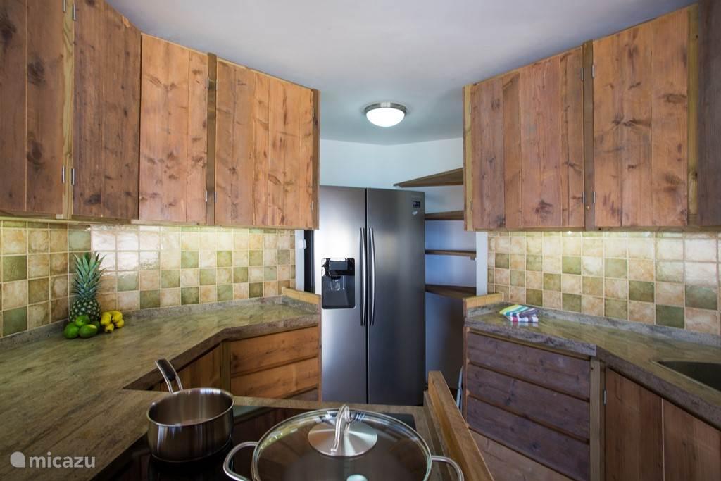 Keuken met fornuis, dubbeldeurs koelkast, ijsblokjesmachine, vaatwasser, oven micro en wave/combi oven.