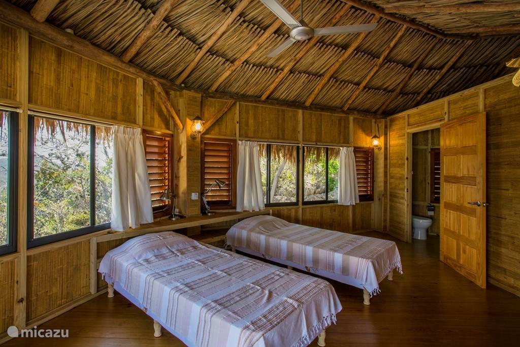 Twee persoons slaapkamer in de grote palapa met plafond fan en prive badkamer.