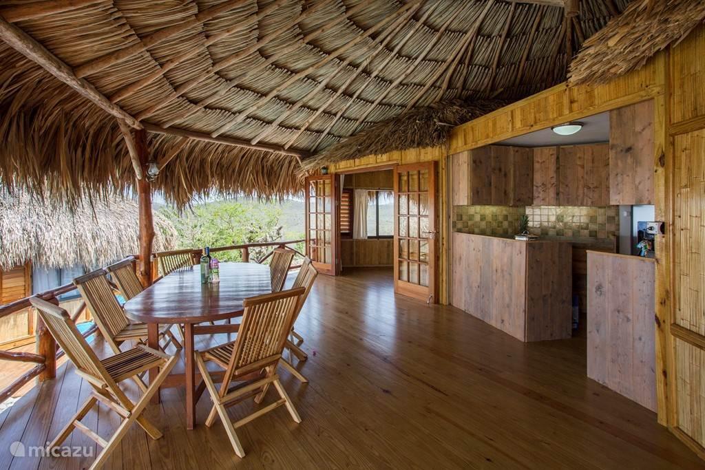 Dinertafel van de grote palapa met de open keuken en de openstaande deuren naar een van de 2 slaapkamers.