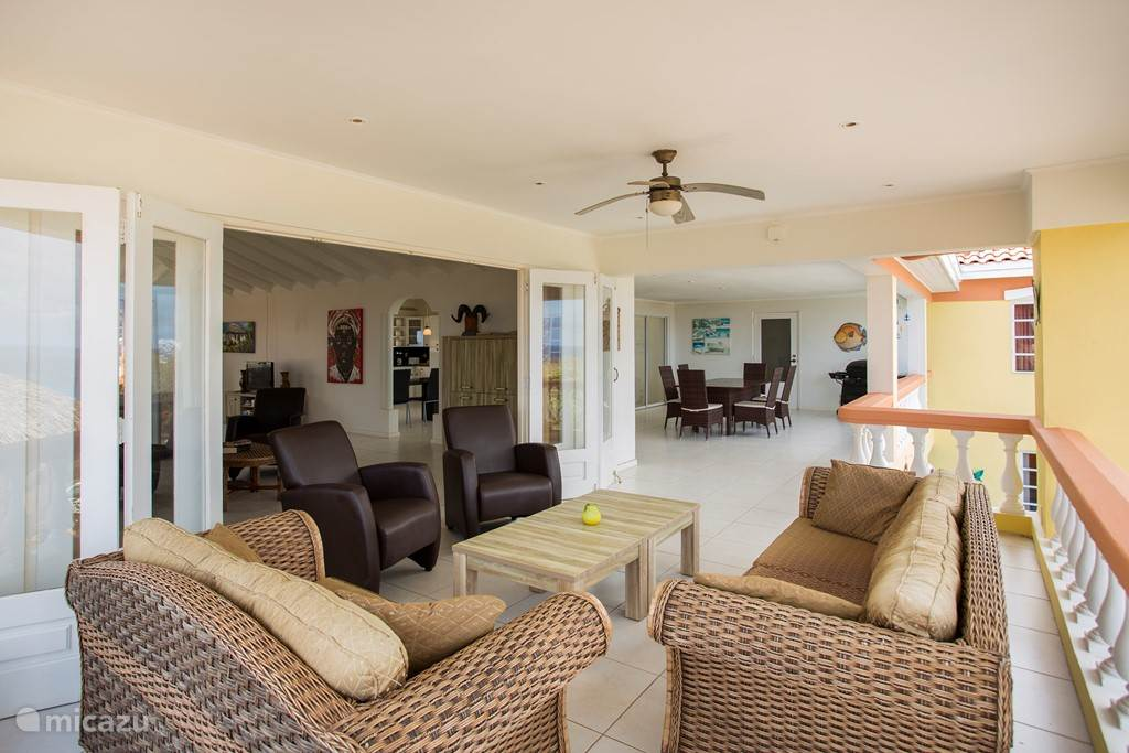 Spacious shady balcony with living area and dining area and bbq.