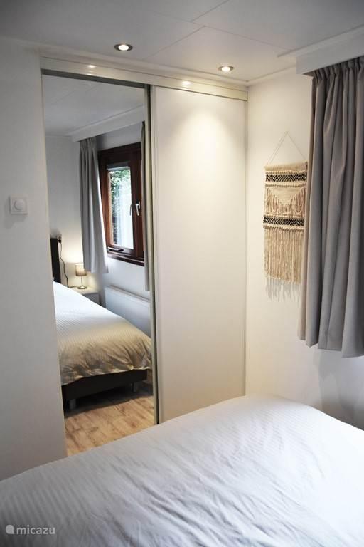 Spiegel en kledingkast in de eerste slaapkamer.