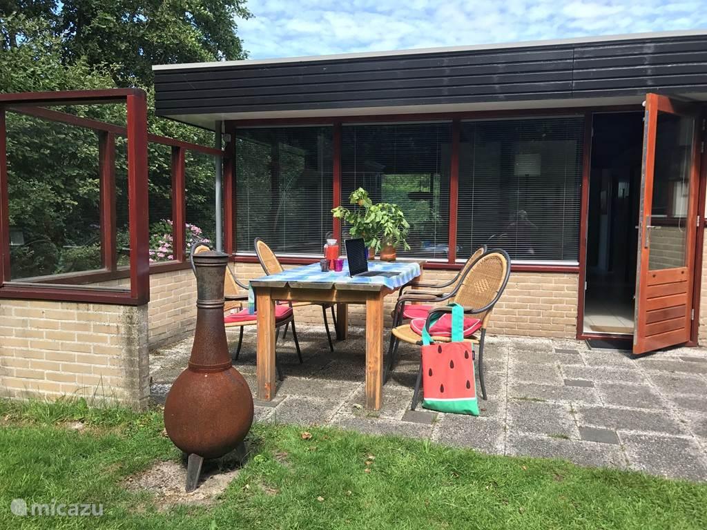 Een zonnig terras achter de bungalow.