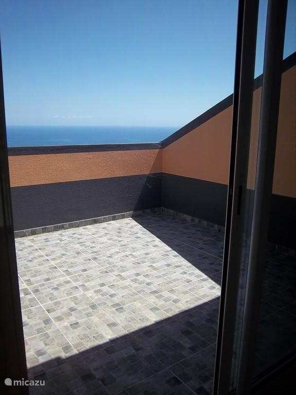 Prive terras van het appartement met zeezicht.