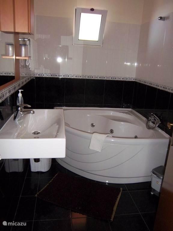 Badkamer bij slaapkamer 1 met oa een jacuzzi