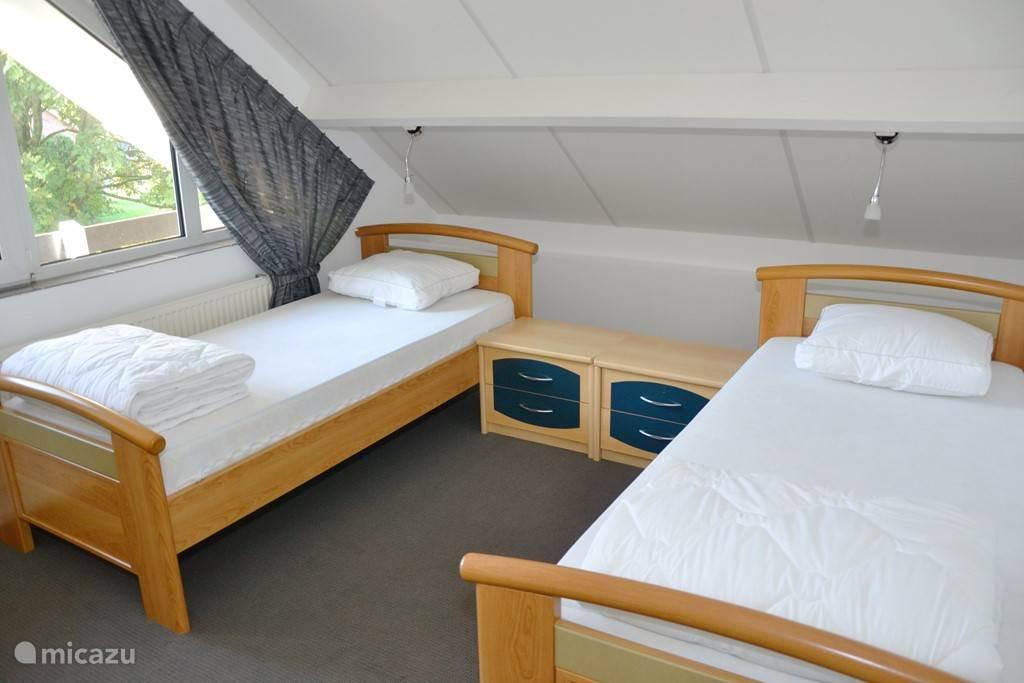 Slaapkamer 2 Ruime slaapkamer met 2 eenpersoons bedden op 1e verdieping met eigen badkamer met douche en wastafel.