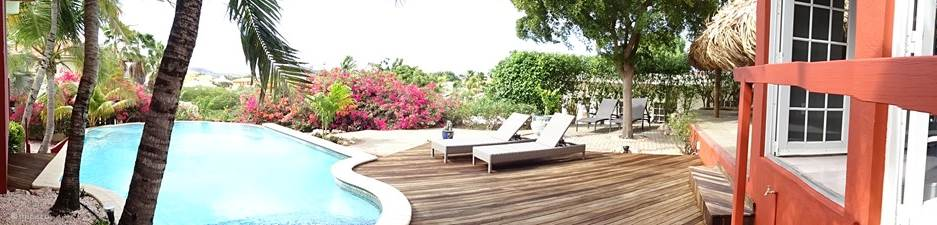 Private pool with pool deck and sun loungers with view on the porch with patio doors