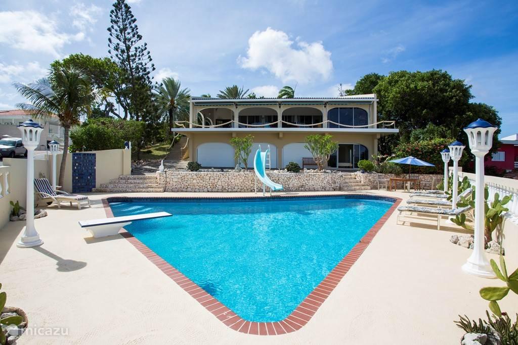 Een ruim driehoekig zwembad in de tropische tuin bij de villa.
