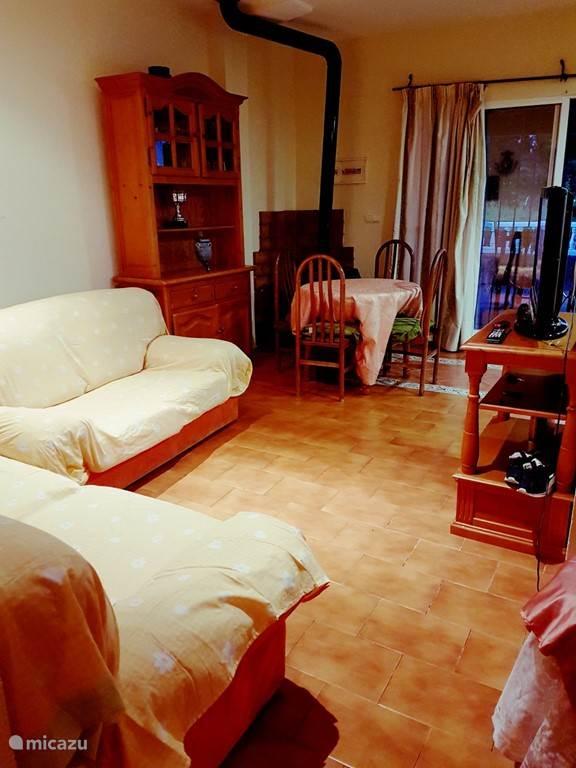 De woonkamer waar ook een bedbank staat