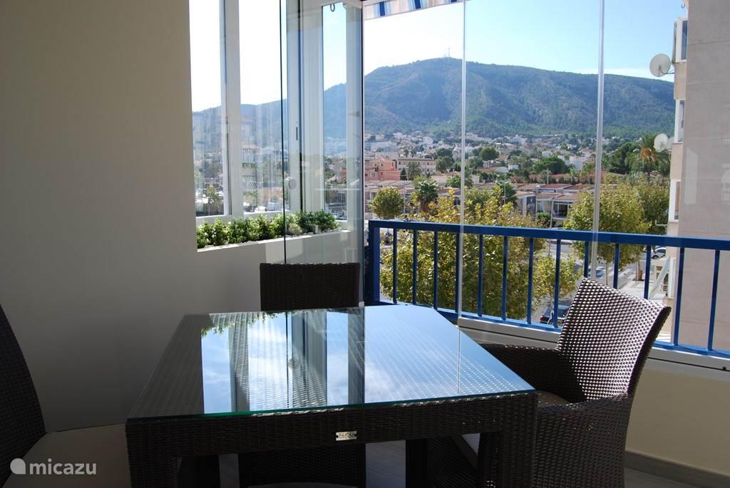 Ingeglaasd terras met een glasgordijn dat makkelijk open of toe te schuiven is. Met een mooi en ruim zicht op het marktplein van Albir en de berg Helada.