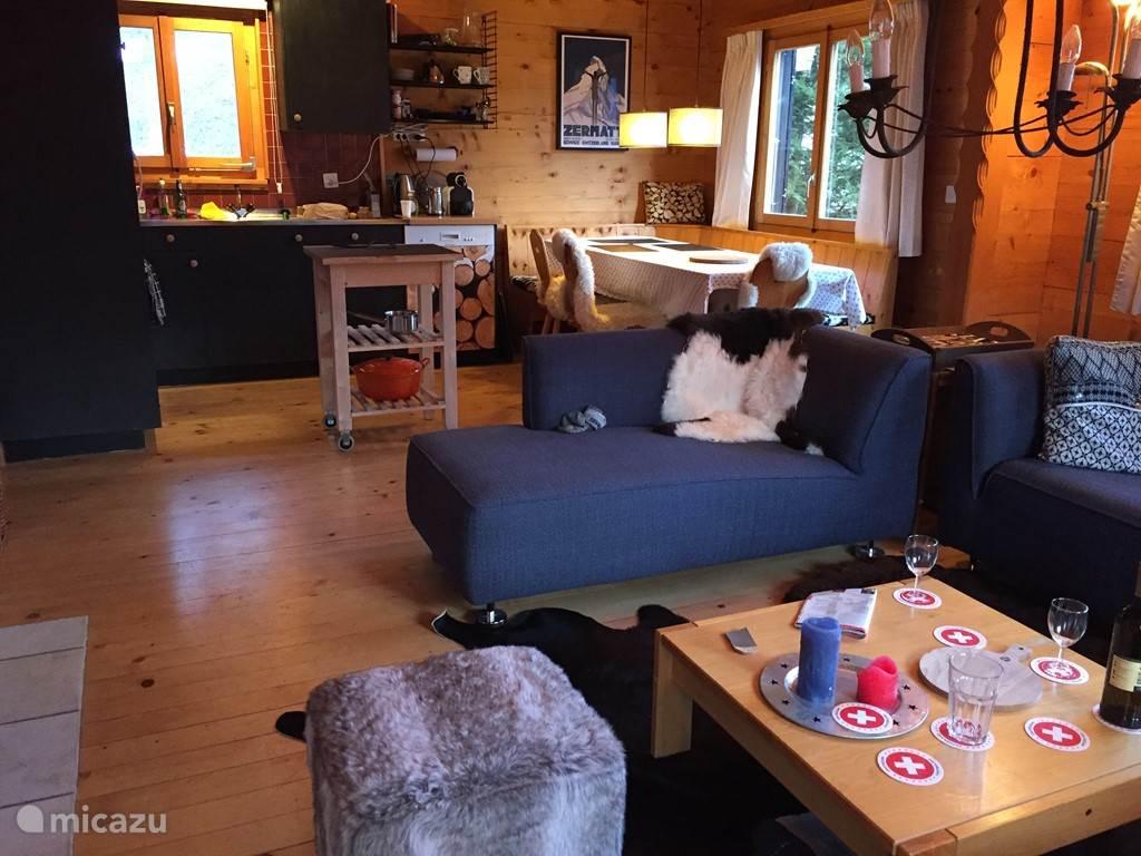 De woonkamer met open keuken en eethoek.