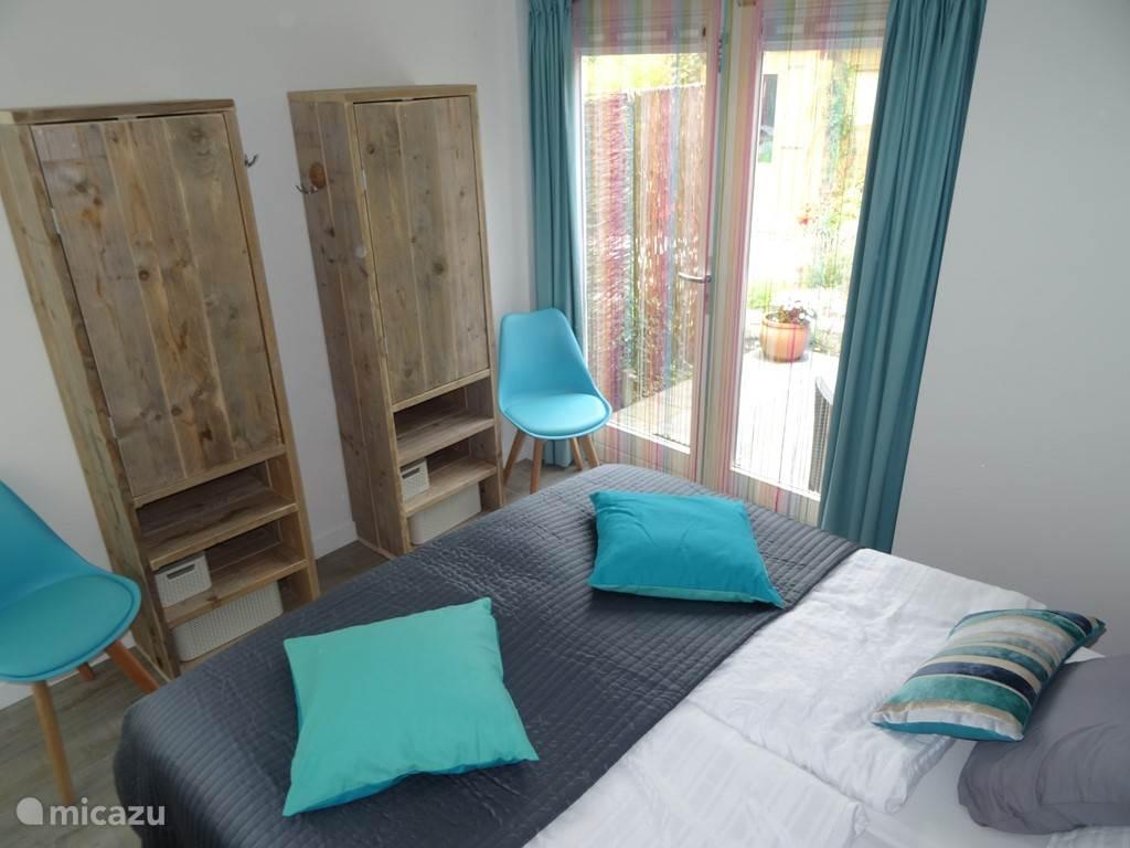 Slaapkamer met 2 boxspringbedden en openslaande deuren naar het achterterras.