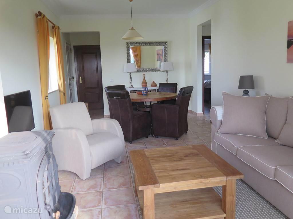 woonkamer met eettafel en vier verrijdbare stoelen