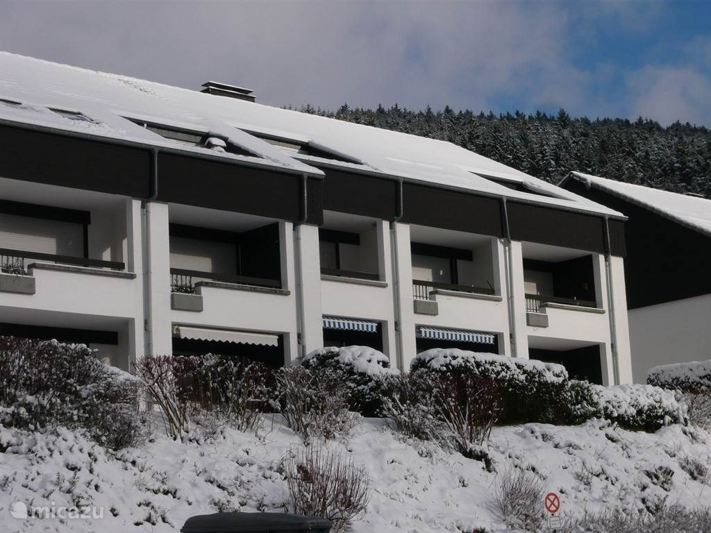 Achterkant van het complex met de zonneschermen met blauw witte strepen voor onze twee terrassen.