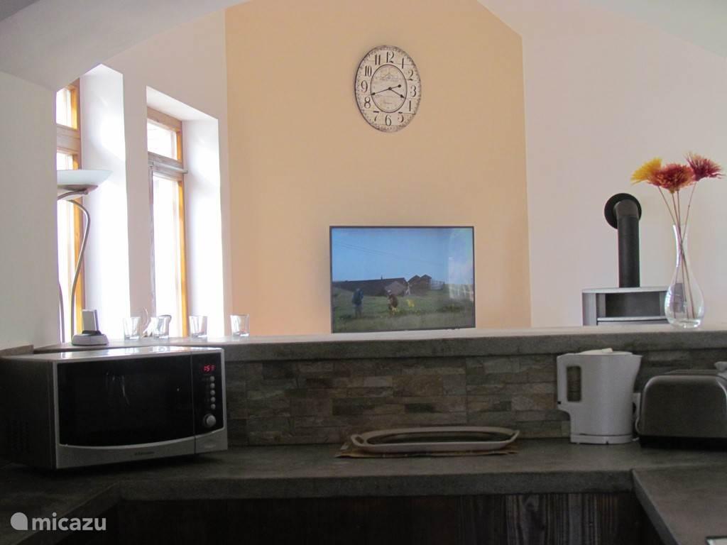 zicht vanuit de keuken op de woonkamer