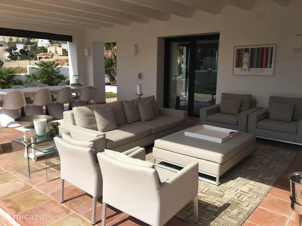 Overdekt terras met buiten salon en eettafel voor 10 personen.