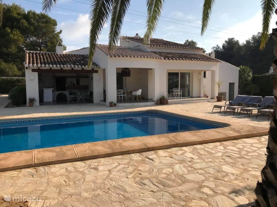 Terras met buitenkeuken, eettafel, woonkamer, zwembad overzicht