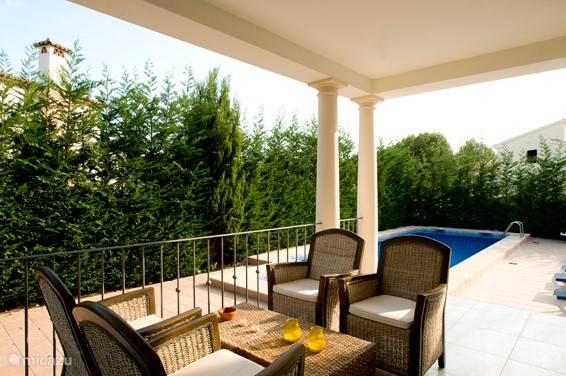 Het terras voor de woonkamer met goed zicht op het zwembad.