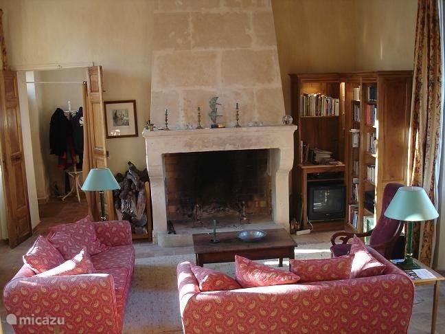 Het woongedeelte van de woon- en eetkamer met originele antieke schouw