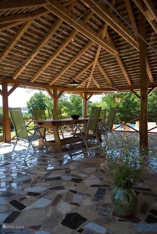 Schaduwrijke veranda met door de lokale houtbewerker gemaakte eikenhouten tafel
