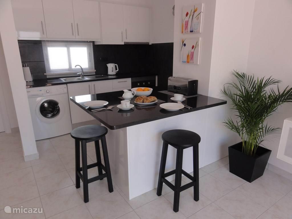Keuken met ontbijtbar met marmeren blad, oven, kookplaat, koelkast met vriesvak, wasmachine, veel kast / lades.