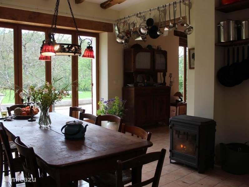 De woonkeuken van huisje La Principale met aangrenzend terras en uitzicht op het weiland.