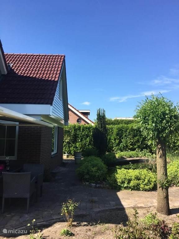 Uitzicht vanaf het terras op de groene tuin met mooie vijver.