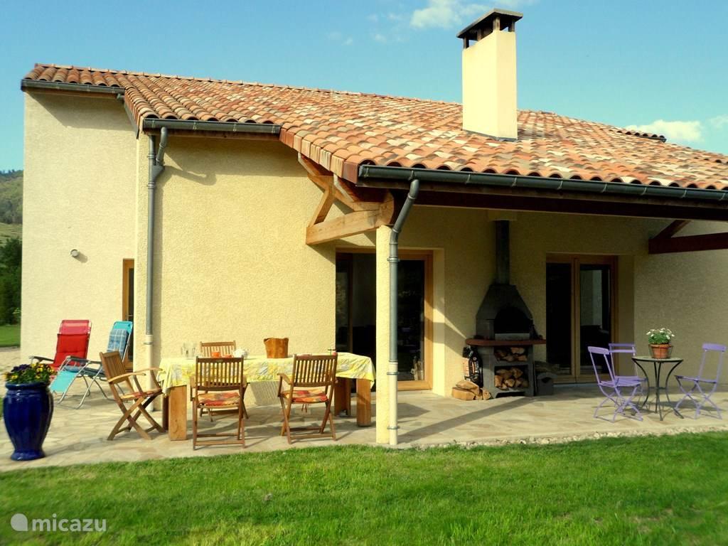 Overdekte veranda met verrijdbare tafel (8 pers.) en buitenhaard / barbecue. De drie terrassen grenzen aan woonkamer en keuken.