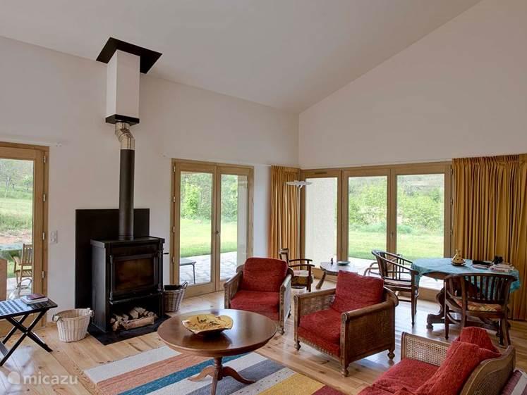 De ruime woonkamer heeft een gevarieerde lichtinval en wordt omringd door drie terrassen. Het huis wordt aangenaam verwarmd door een Janus-houtkachel.