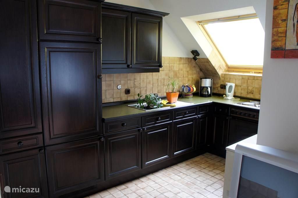 Ruime en complete keuken voorzien van oven, koelkast met vriesvak, koffiezetapparaat, waterkoker en 4-pits elektrisch fornuis met afzuigkap