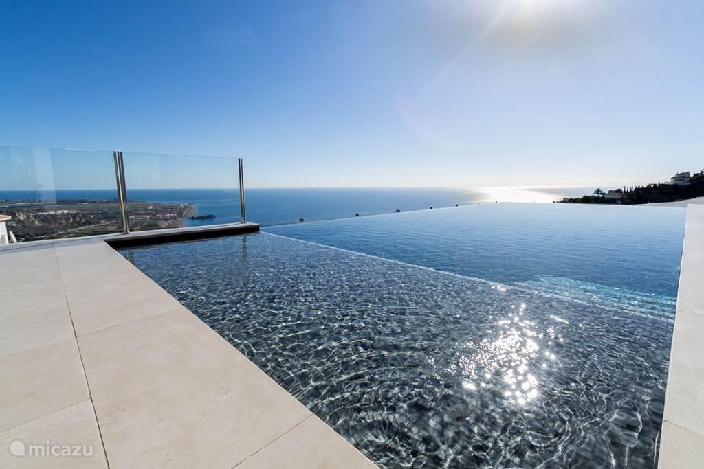 Het infinity' zwembad lijkt naadloos over te lopen in de Middellandse Zee.