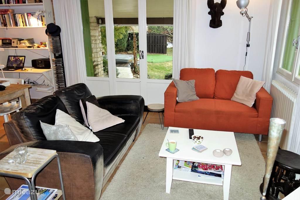 De gezellige woonkamer, met zitbanken, eettafel, bureautje en TV.