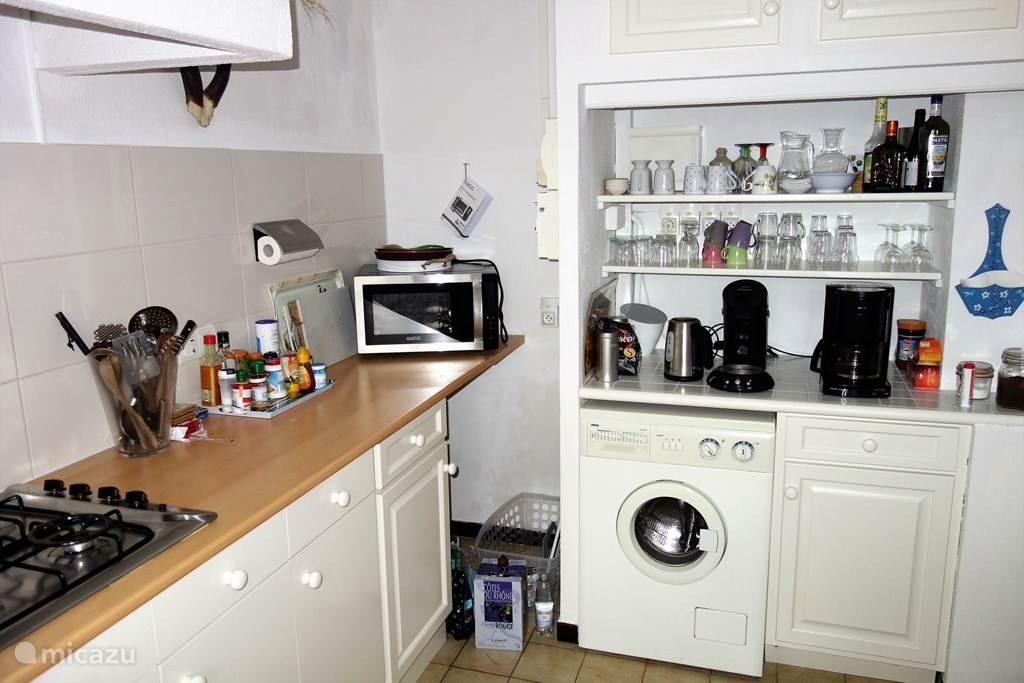 De ruime keuken met eettafel, gasfornuis, combi-magnetron, koelkast en wasmachine.