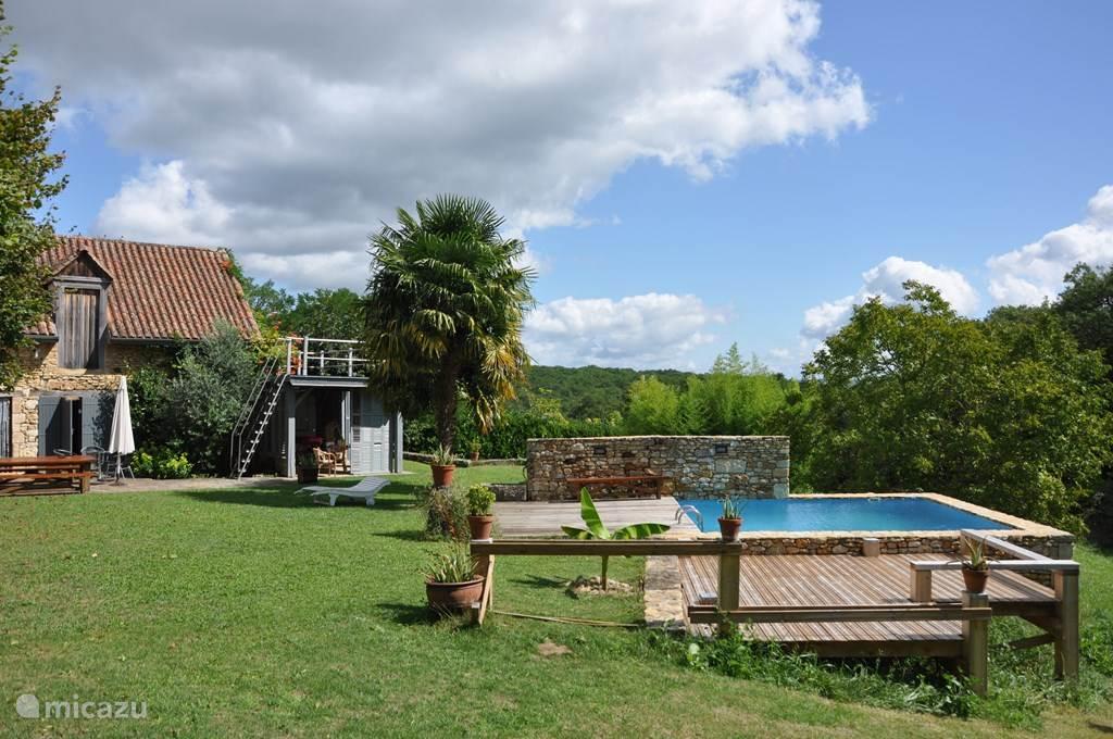 Zonnige tuin met zwembad