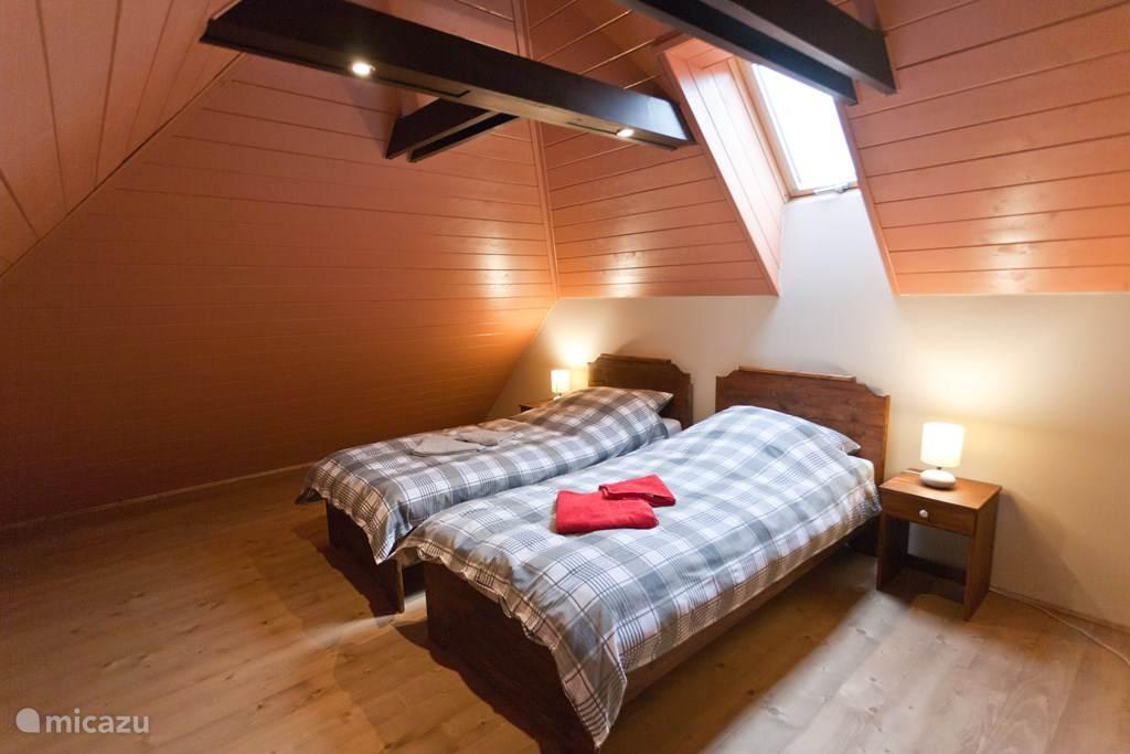 De slaapkamer op eerste verdieping heeft een knusse sfeer met houten lambrisering en een klapraam.