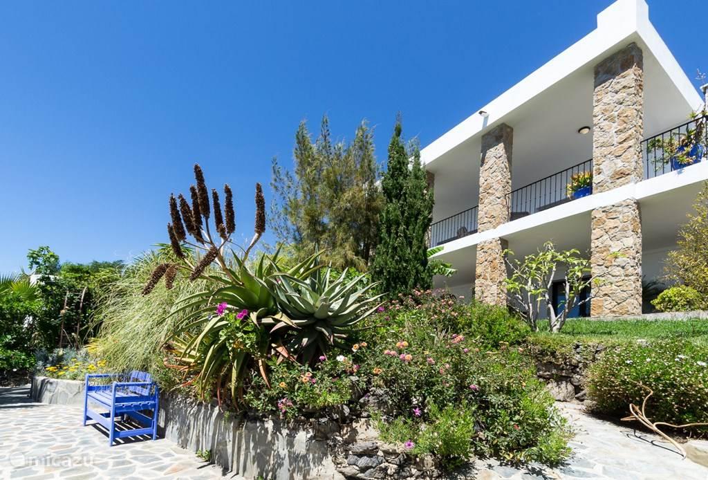 De villa wordt omgeven door een tropische tuin.