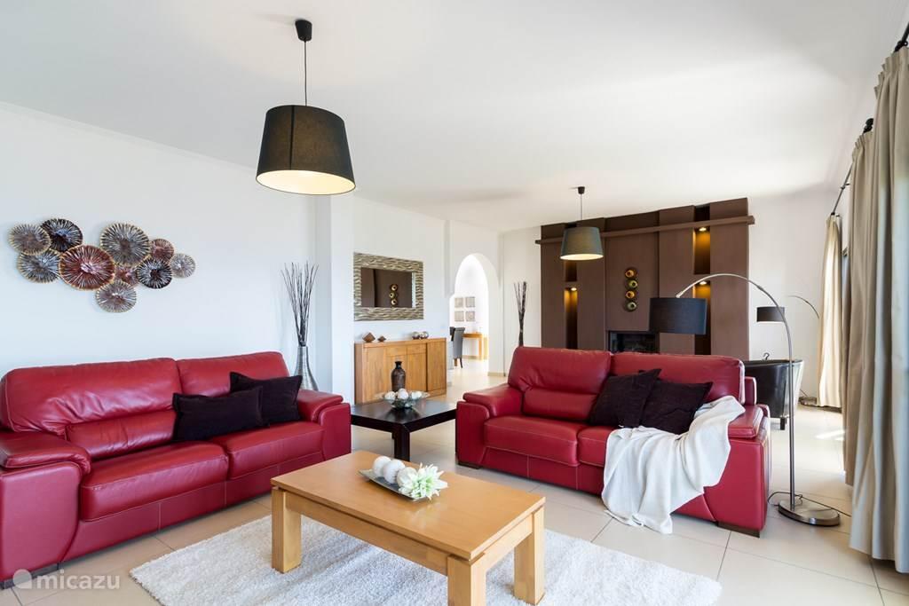 Royale woonkamer met twee zithoeken rond de TV en de open haard.