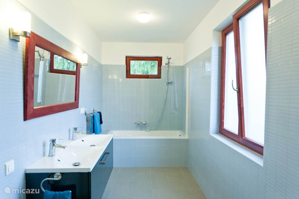 Deze badkamer is voorzien van toilet, dubbele wastafels en ligbad.