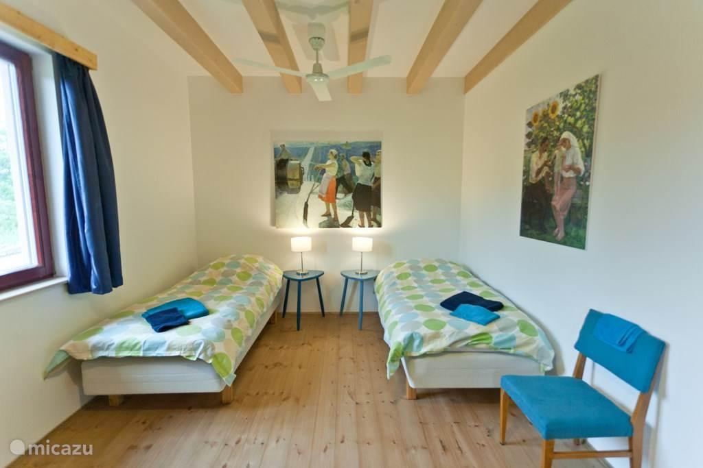 De slaapkamer beschikt over comfortabele bedden en een ruime kledingkast en biedt directe toegang tot de belendende badkamer.