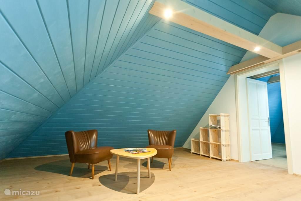 In het zithoekje op de bovenverdieping kunt u zich terugtrekken om te lezen of een spelletje te doen.